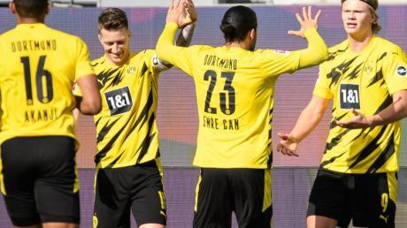 Dortmunds Matchwinner Erling Haaland (r) wird von seinen BVB-Teamkollegen in Wolfsburg gefeiert.