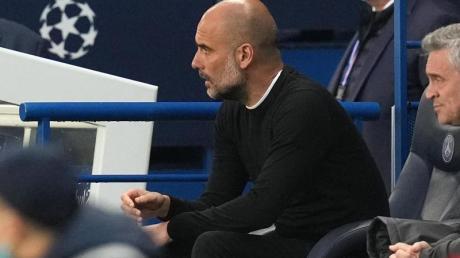 Pep Guardiola, Trainer von Manchester City, sitzt auf der Bank und beobachtet das Spiel.