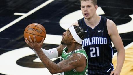 Marcus Smart (l) von den Boston Celtics setzt zum Wurf an. Moritz Wagner (21), Spieler bei Orlando Magic, versucht ihn zu decken.