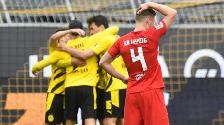 Leipzigs Abwehrspieler Willi Orban fasst sich nach der Niederlage beim BVBan den Kopf - im Hintergrund feiern die Dortmunder Spieler den Sieg.