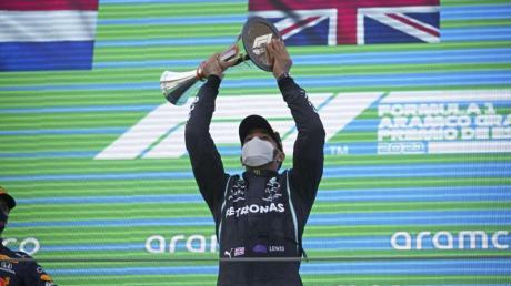 Lewis Hamilton (r) bejubelt seinen Sieg auf dem Podium. Max Verstappen (l) steht als Zweiter daneben.