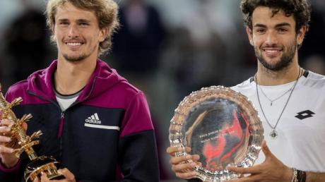 Madrid-Sieger Alexander Zverev (l) und der Zweitplatzierte Matteo Berrettini erhalten ihre Trophäen während der Siegerehrung.