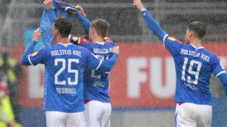 Die Kieler Spieler Phil Neumann (l-r), Hauke Wahl und Simon Lorenz halten nach dem Treffer zum 1:1 ein Trikot des verletzten Mannschaftskameraden Ahmet Arslan hoch.