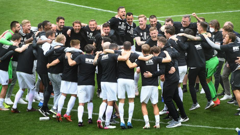 Jubel-Rudel am Mittelkreis: Spieler, Trainer und Betreuer des FC Augsburg feiern den Klassenerhalt in der Fußballbundesliga.