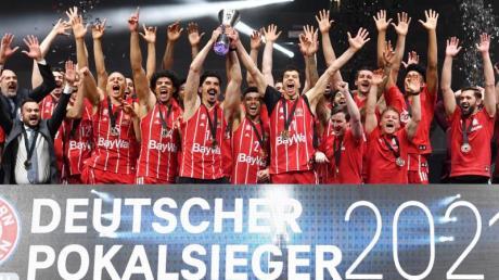 Die Bayern jubeln nach dem Spiel mit der Trophäe.
