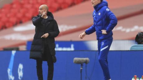 Pep Guardiola (l) trifft mit Manchester City auf Thomas Tuchel und den FC Chelsea.