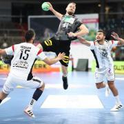 Deutschlands Julius Kühn (M) holt zwischen den Ägyptern Ahmed Mohamed (l) und Yehia El-Deraa zum Wurf aus. Handball-EM 2022 live in Fernsehen & Stream - Free-TV in ARD und ZDF?