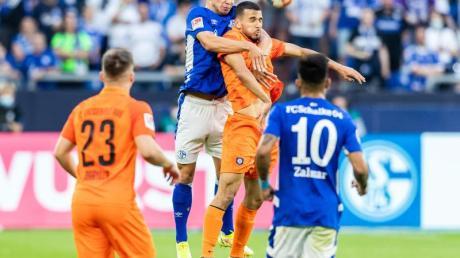 Schalkes Mehmet Aydin (2.v.l.) und Aues Soufiane Messequem (2.v.r.) gehen zum Kopfballduell hoch.