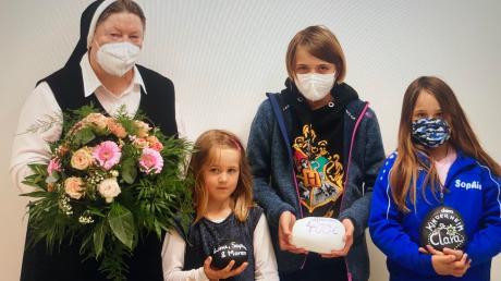 Schwester Maria Elisabeth bei der Übergabe der Spende mit den Schwestern Maren, Lina und Sophie (von links).