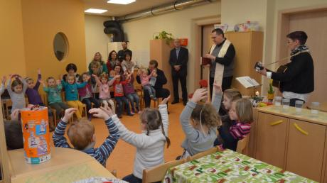 In freundlichem Orange ist das neue Zimmer der Mäusegruppe gehalten, hier bei der Segnung durch Pfarrer Rupert Ostermayer (Zweiter von rechts stehend).