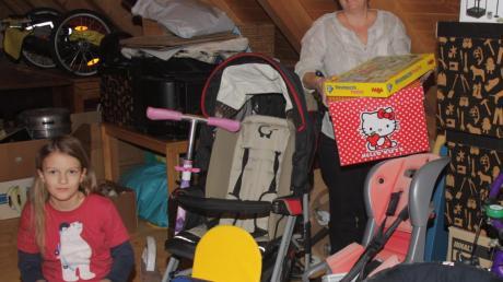 Auf dem Dachboden von Birga Wendt (mit Tochter Rika) in Roggden stapeln sich Kinderkleidung, Kinderwagen und Autositze, die im Tauschkreis die Runde machen.