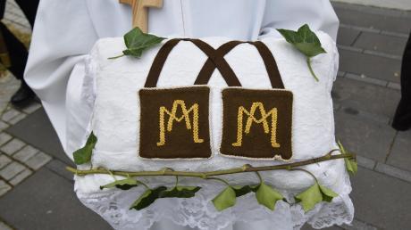 Während der Prozession wird in Binswangen das Kissen mit den Skapulieren getragen: Zwei Stoffläppchen, die durch Bänder verbunden sind. Diese symbolisieren das Schulterkleid von Ordensgewändern.