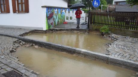 So sah es unterhalb es Kindergartens Sonnenscheins am Kalteck in Wertingen aus. In dem Gebäudekomplex (Hintergrund rechts) stand der Keller im Altbau unter Wasser. Engagierte Eltern reagierten rasch und brachten sogar Pumpen mit. Unser Bild zeigt das weggespülte Pflaster und eine Passantin.