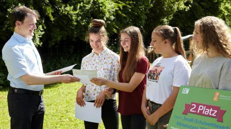 """Thomas Luy von der Bildungsinitiative """"3malE"""" übergibt den Preis an die Schülerinnen der Privaten Montessori-Schule Wertingen."""