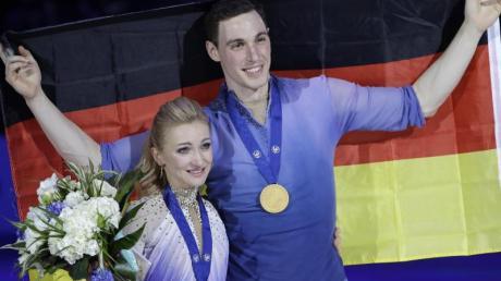Weltmeister mit Bestnote: Aljona Savchenko und Bruno Massot mit Medaillen und Fahne.