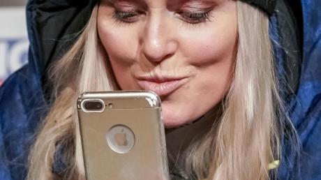 Lindsey Vonn spricht bei der Pressekonferenz zu ihrem Karriereende in ihr Handy und gibt Küsse.