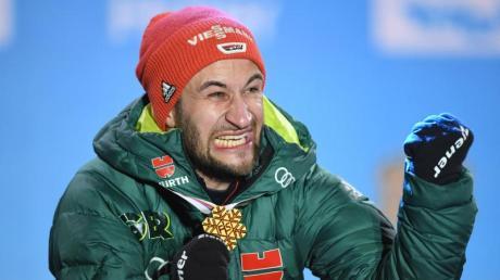 Skiskringer Markus Eisenbichler freut sich bei der Siegerehrung über seiner WM-Goldmedaille. Foto: Hendrik Schmidt