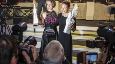 Magdalena Neuner (l) und Laura Dahlmeier halten ihren Pegasos-Preis in der Kategorie «Legende des Sports» in die Höhe.