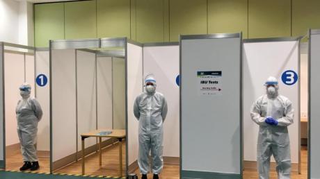 Helfer stehen in einem Corona-Testzentrum der IBU für Tests im Rahmen des Hygiene-Konzepts bereit.