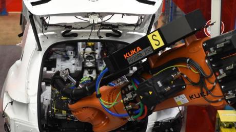 Ein Roboterarm von Kuka im Mercedes-Benz-Werk in Bremen setzt eine Batterie in ein C-Klasse Hybrid Modell.