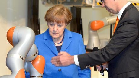 Da waren die Zeiten noch in Ordnung: Ex-Kuka-Chef Reuter zeigte Kanzlerin Merkel im Jahr 2015 Hightech aus Augsburg. Sich statt chinesischer Investoren an der Firma zu beteiligen, davor schreckte der Bund aber zurück.