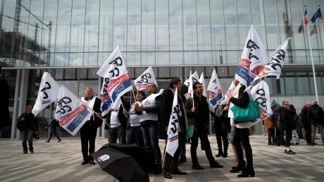 Gewerkschaftsvertreter protestieren am ersten Prozesstag vor dem Gerichtsgebäude.