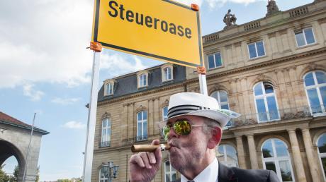 Dieses Foto aus Stuttgart ist natürlich Satire. Es spielt darauf an, dass in manchen Ländern der Steuersatz extrem niedrig oder nicht vorhanden ist. Für Privatpersonen genauso wie für Unternehmen. Doch die Debatte darüber, was Firmen in Deutschland zahlen müssen, sollte geführt werden, finden Experten.