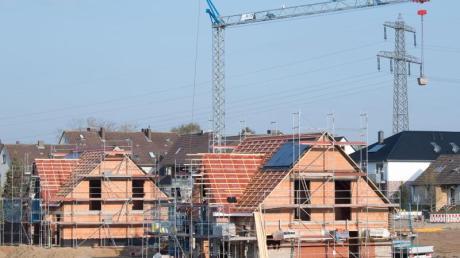 Einfamilienhäuser stehen im Rohbau in einem Neubaugebiet. Foto: Julian Stratenschulte/Illustration