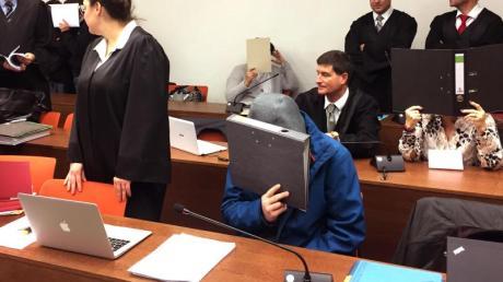 Angeklagte (verdeckt) sitzen neben ihren Verteidigern im Gerichtssaal des Landgerichts München.