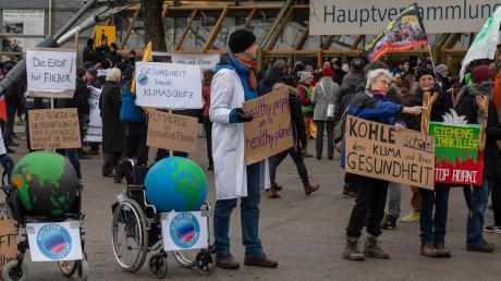 Die kranke Erde im Rollstuhl: Klima-Aktivisten demonstrieren vor der Olympiahalle in München, wo die Siemens-Hauptversammlung stattfindet.