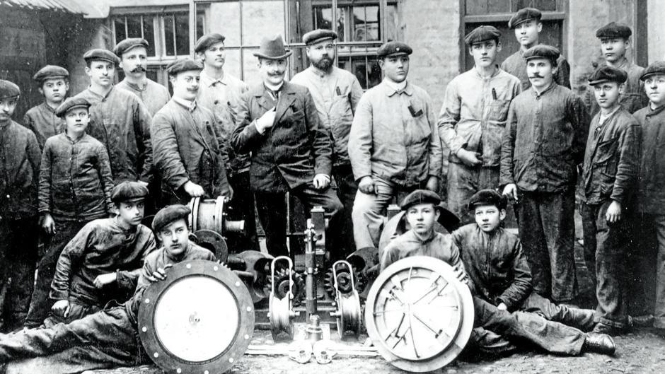 Die Hosokawa Alpine wurde 1898 als Otto Holzhäuer'sche Maschinenfabrik in Augsburg gegründet. Das Bild entstand um 1900.