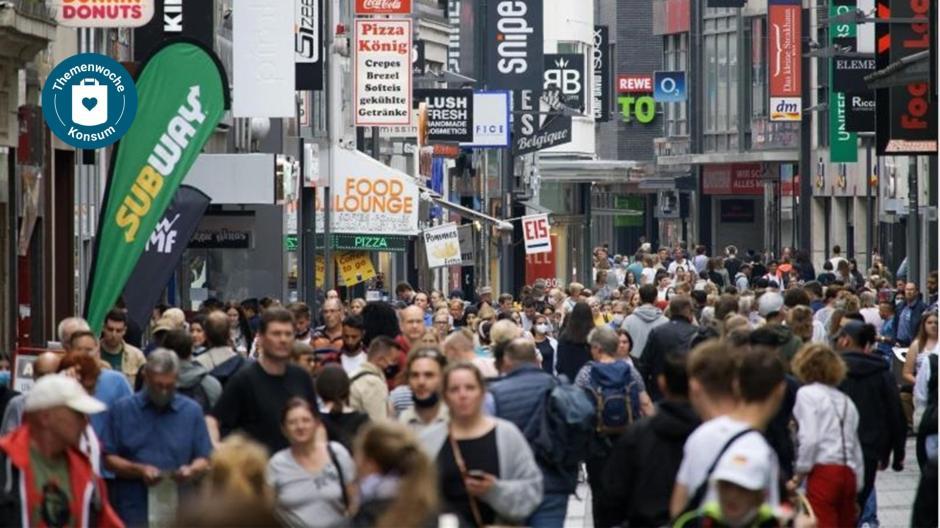 Passanten bummeln auf einer Shoppingmeile. Macht Kaufen wirklich glücklich?