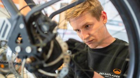 Im Februar hat er seine Ausbildung zum Zweiradmechatroniker abgeschlossen: Stefan Borschert setzt ein neues Hinterrad an einem E-Lastenrad ein.