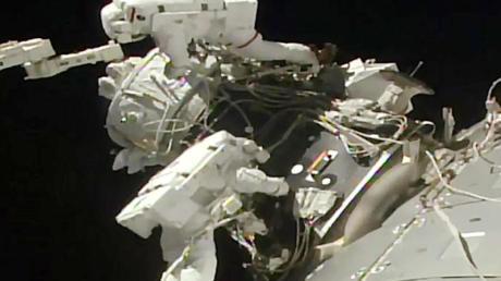 Astronautenbei der Installation eines einen Adapters an der ISS.
