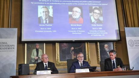 Der Nobelpreis für Physik geht in diesem Jahr an James Peebles (l-r auf der Leinwand), Michel Mayor und Didier Queloz. Foto: Claudio Bresciani/TT NEWS AGENCY/AP/dpa