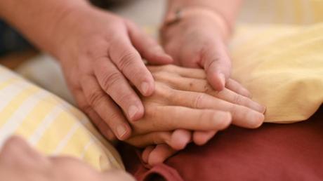 Eine Hospizmitarbeiterin hält die Hand eines todkranken Menschen, der im Hospiz im Bett liegt. Foto: Felix Kästle/dpa