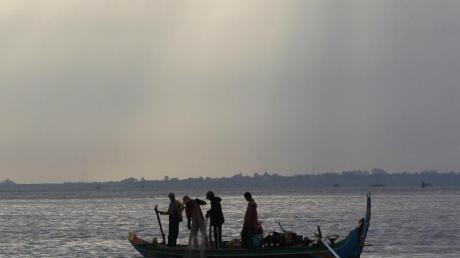 Kambodschanische Fischer fahren auf dem Mekong-Fluss in Phnom Penh mit ihrem Boot.