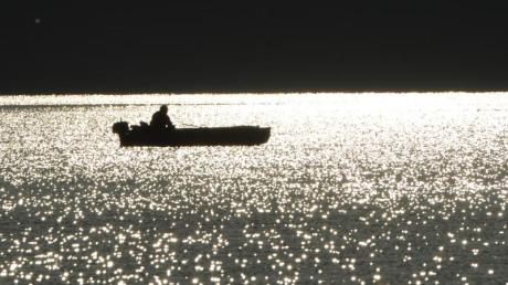 Ein Angler sitzt bei Sonnenaufgang in seinem Boot auf dem Bodensee bei Bodman.