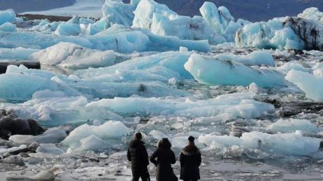 Touristen stehen vor Eisbergen in der Gletscherlagune Jökulsarlon im Süden Islands. Foto: Owen Humphreys/PA Wire/dpa