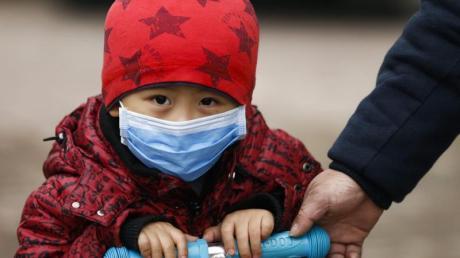 Ein Kind in Peking trägt zum Schutz vor Smog eine Atemmaske. Foto: Rolex Dela Pena/EPA/dpa