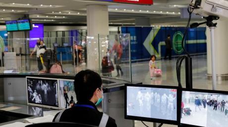 Ein Beamter der Gesundheitsüberwachung überwacht mit Wärmebildkameras die Temperatur von Reisenden am Flughafen von Hongkong ankommenden Reisenden.