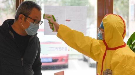Sorge vor dem Virus: Ein Beamter misst bei einem Kunden eines Friseursalons in China die Temperatur.