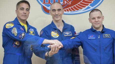 Nasa-Astronaut Christopher Cassidy (l) und die russischen Kosmonauten Anatoli Iwanischin (M) und Iwan Wagner bei einer Pressekonferenz im Weltraumbahnhof Baikonur hinter Schutzglas.