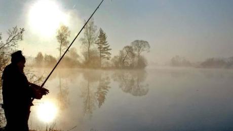 Ein Angler an einem Baggersee in Bayern.