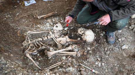 Kreisarchäologe und Grabungsleiter Jürgen Hald gräbt Teile von Skeletten an der historischen Hinrichtungsstätte aus.