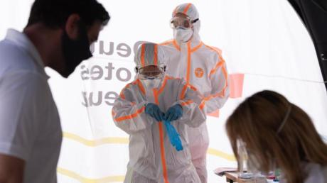 Zwei Mitarbeiter des Deutschen Roten Kreuzes (DRK) in Schutzkleidung in einer mobilen Covid-19-Beprobungsstation.