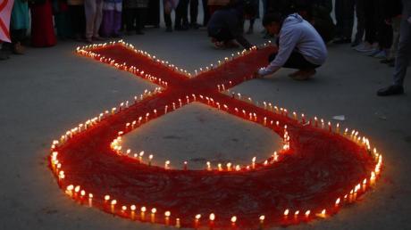 Aktivisten stellen auf einer Veranstaltung im Vorfeld des Welt-Aids-Tags Kerzen auf, die eine rote Schleife formen - ein weltweit anerkanntes Symbol für die Solidarität mit HIV-Infizierten.