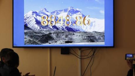 Nepalesische Regierungsbeamte schauen eine gemeinsame Fernsehübertragung von Nepal und China, in der die offizielle Höhe des Mount Everests bekanntgegeben wird.