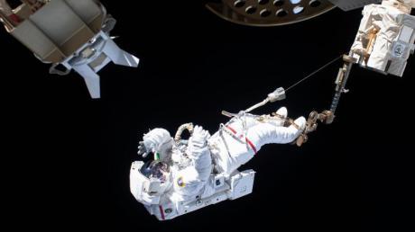 Der ESA-Astronaut Luca Parmitano ist bei einem Außeneinsatz an der Internationalen Raumstation ISS über den Roboterarm Canadarm2 gesichert.