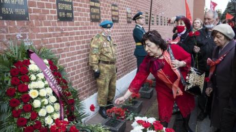 Menschen stehen Schlange, um Blumen am Grab von Juri Gagarin in der Kreml-Mauer niederzulegen.